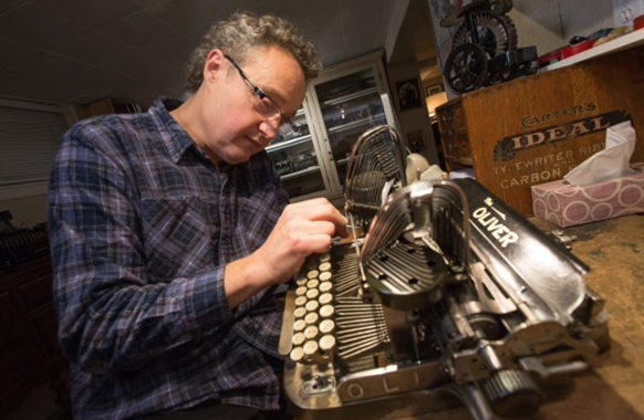 Photograph showing Martin Howard working on an Oliver 2 typewriter.