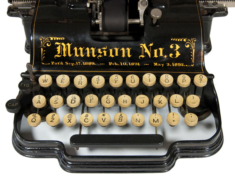 Photograph of the Munson 1 typewriter showing a close up of the keyboard and the decorative front panel.