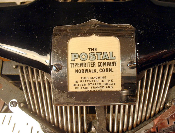 Photograph of the Postal 3 typewriter showing a close up view of the top name plate.