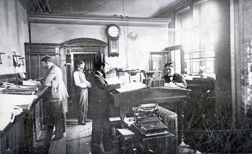 Photograph of an office scene showing clerks still handwriting in the presence of a Caligraph typewriter.