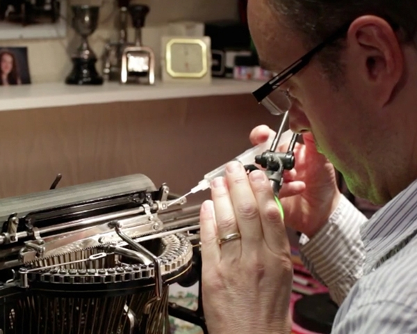 A photograph showing Martin Howard restoring an antique typewriter.
