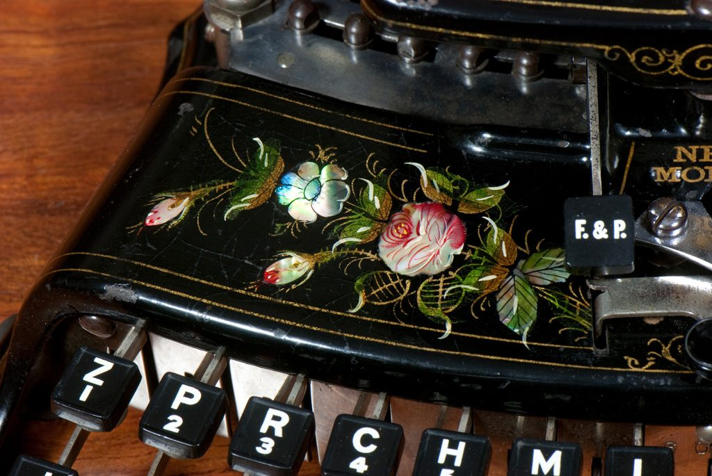 Photograph of the Crandall New Model typewriter showing the hand painted roses adorning the frame.