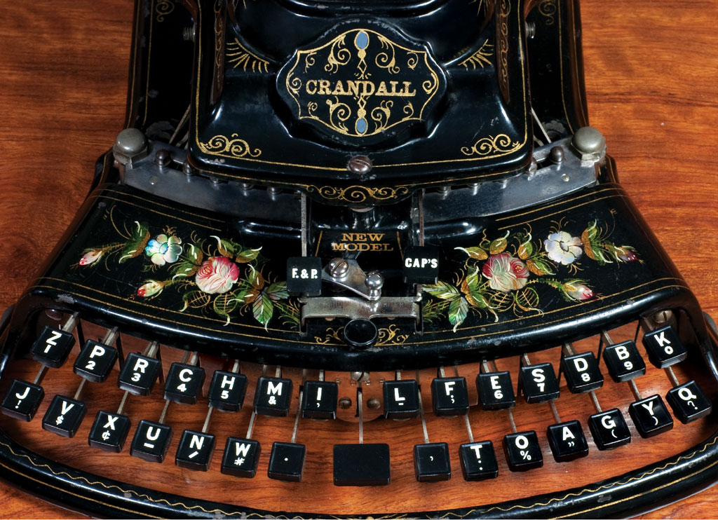 Photograph of the Crandall New Model typewriter showing the keyboard and the beautiful floral decorations adorning the front of the frame.